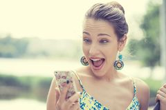 Surprised screaming young girl looking at mobile phone Stock Images