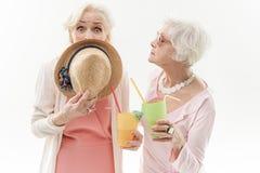 Surprised senior ladies drinking beverage on vacation Royalty Free Stock Photos