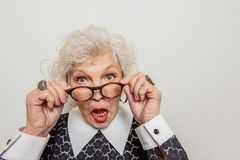 Surprised senior lady adjusting her glasses. Waist up portrait of shocked old woman staring at something with open mouth. She is standing and touching her stock photography
