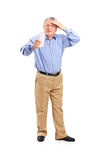 Surprised senior looking at store receipt. Full length portrait of a surprised senior looking at store receipt on white background royalty free stock photography