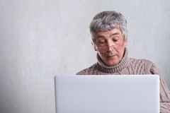 A surprised senior man dressed in sweater having gray hair and wrinkles using his laptop surfing in the internet. A lonely handsom. E grandfather reading news Royalty Free Stock Photography