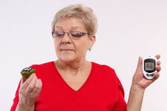 Surprised senior woman holding glucometer and fresh cupcake, measuring and checking sugar level, concept of diabetes Royalty Free Stock Images