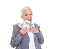 Surprised senior woman with money. Happy senior woman holding many Euro banknotes Stock Photography