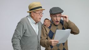 Surprised seniors looking at documents in disbelief stock footage
