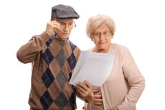 Surprised seniors looking at documents. Isolated on white background Royalty Free Stock Image