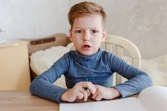 Surprised serious boy sitting at his Desk Stock Photos