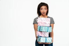 Surprised shocked african woman holding stack of present boxes Royalty Free Stock Images
