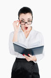 Surprised, shocked businesswoman holding glasses and looking for. In a notebook even more closely Stock Images