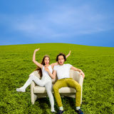 Surprised and shocked couple sitting on the couch  Royalty Free Stock Photo