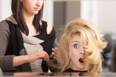 Surprised shocked female client blond girl in hairdressing salon Stock Photography