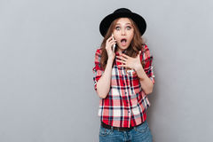 Surprised shocked girl in plaid shirt talking on mobile phone Stock Image