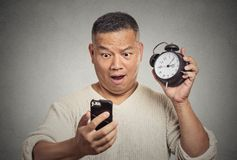 Surprised shocked man with alarm clock looking at smart phone Royalty Free Stock Photos