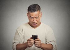 Surprised shocked pissed off man unhappy by what he sees on cellular phone Stock Image