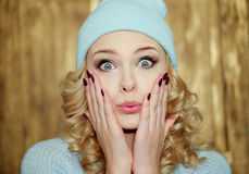 Surprised or shocked woman with blue eyes. Surprised or shocked attractive young blond woman with ringlets and huge blue eyes holding her hands with manicured Royalty Free Stock Image