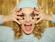 Surprised or shocked woman with blue eyes. Surprised or shocked attractive young blond woman with ringlets and huge blue eyes holding her hands with manicured Stock Photo