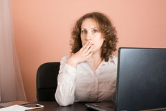 Surprised/shocked woman sitting in office and using laptop Stock Images