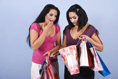 Surprised shopping woman. Two friends women with shopping bags,one showing her friend contents of the bag  and the girl look  surprised and smiling.Check also Royalty Free Stock Photo