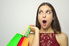 Surprised shopping woman looking to the side the copy space on white background.  Stock Photos