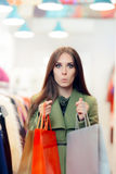 Surprised Shopping Woman Wearing a Green Coat in Fashion Store Stock Photo
