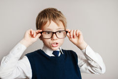 Surprised smart boy in big glasses staring at the camera. Education. Objects over white. Portrait of little boy in business suit with shocked expression Stock Photography