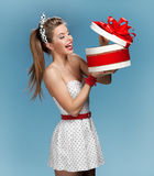 Surprised smiling beautiful young woman holding an open gift box and looking at the present. Holidays, holiday, celebration, birth Royalty Free Stock Photography