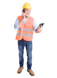 Surprised and smiling engineer using smartphone and tablet. In multitasking mode Royalty Free Stock Photo