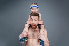 Surprised smiling father holding his little son on shoulders. Surprised smiling father with opened mouth holding his little son on his shoulders over grey Royalty Free Stock Images