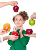 Surprised smiling girl choosing  proposed apples Royalty Free Stock Photos