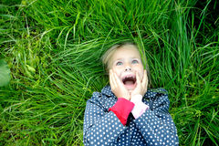 Surprised smiling little girl. Lyinng on grass Royalty Free Stock Image