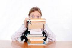 Surprised student. Pretty female student surprised and scared of how many books she has to study Stock Photography