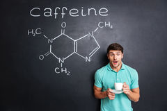 Surprised student drinking coffee over drawn structure of caffeine molecule Stock Image