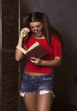 Surprised student girl reading a book. young woman in red top and denim shorts with glasses.  Royalty Free Stock Images
