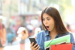 Surprised student girl watching phone content royalty free stock images