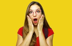 Surprised student with glasses on a yellow background stock photography