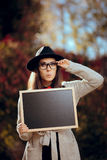 Surprised Student Holding a Blackboard Sign Sale Announcement. First school day concept image of a girl with blank board announcement in autumn décor stock photo