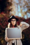 Surprised Student Holding a Blackboard Sign Sale Announcement. First school day concept image of a girl with blank board announcement in autumn décor royalty free stock photo