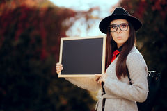 Surprised Student Holding a Blackboard Sign Sale Announcement. First school day concept image of a girl with blank board announcement in autumn décor royalty free stock photos