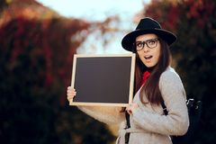 Surprised Student Holding a Blackboard Sign Sale Announcement. First school day concept image of a girl with blank board announcement in autumn décor stock image