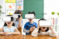 Surprised students with virtual reality headset. In classroom Stock Images