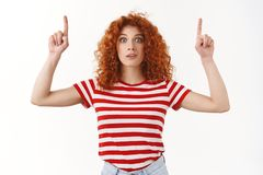 Surprised stunned redhead attractive curly-haired woman wide eyes hold breath amused pointing up index fingers look. Questioned impressed unbeliavable royalty free stock photos