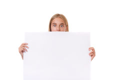 Surprised teen girl behind empty board, isolated Stock Photos
