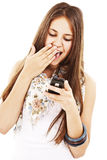 Surprised teen girl looking at the mobile phone Stock Images