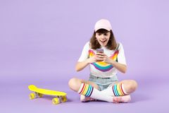 Surprised teen girl in vivid clothes sitting near skateboard using mobile phone typing sms message isolated on violet