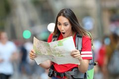Surprised teen tourist reading a guide Royalty Free Stock Photo