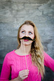 Surprised Teenage Gil holding funny mustache on stick. Stock Photos