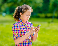 Surprised teenage girl in casual clothes with smartphone. In her hand, looking at screen, reading a message, using Facebook, texting and chatting stock photography