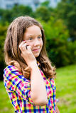 Surprised teenage girl in casual clothes speaking by cell phone Stock Photo