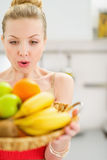 Surprised teenage girl holding plate of fruits Royalty Free Stock Photo