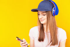 Surprised teenage girl uses a headphones and mobile phone Stock Photography