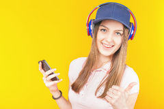 Surprised teenage girl uses a headphones and mobile phone Stock Images